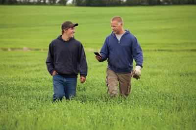 Father and son walking through a </p> <p>field, father on the phone